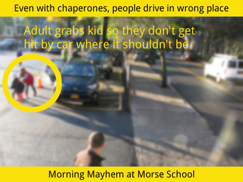 Screen capture of video. Morning Mayhem at Morse School. Shows an adult grabbing a child so they don't get hit by a car.