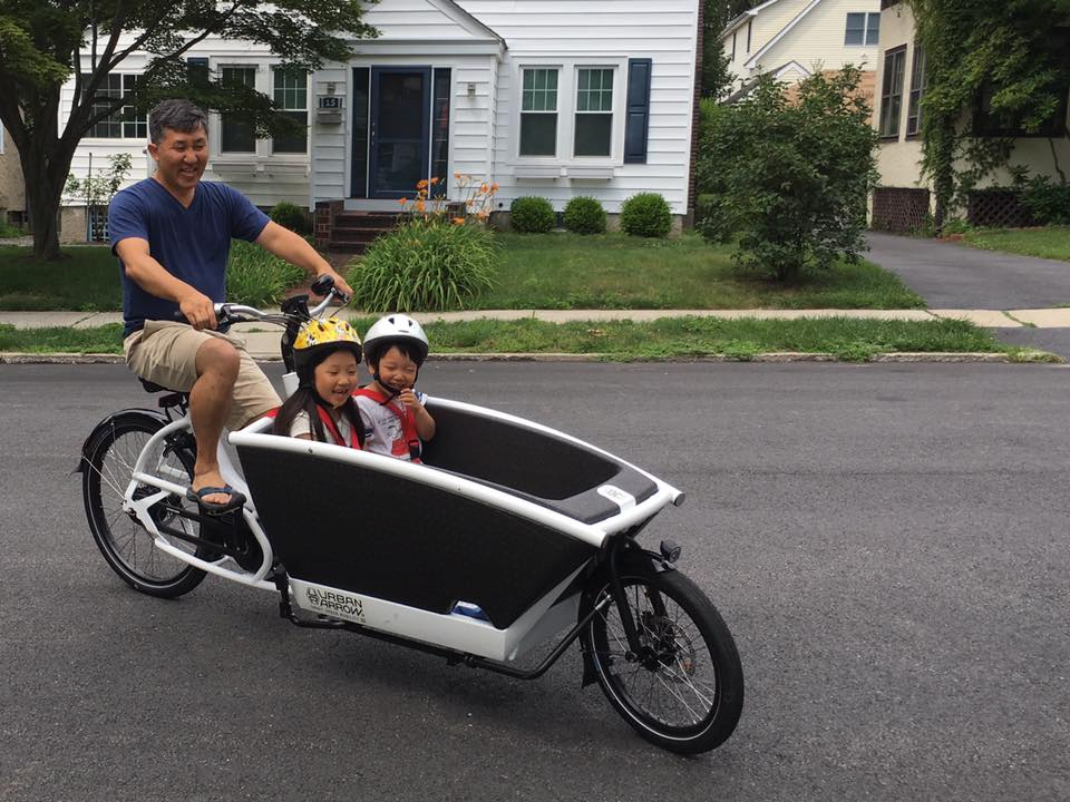 Person riding an ebike cargo bike with kids in it.